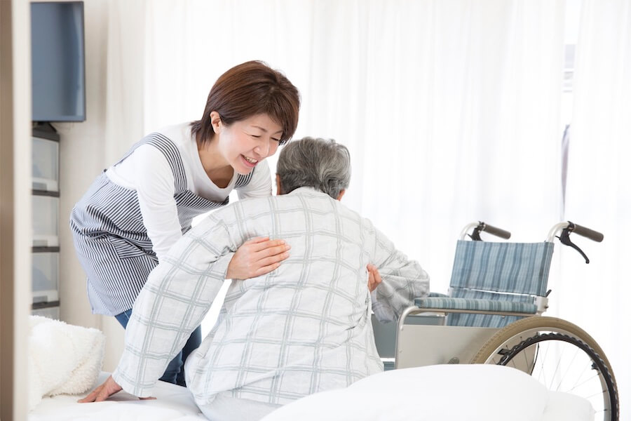 asian lady helping older lady to wheelchair
