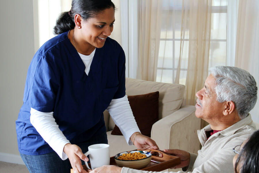 nurse serving food to older man
