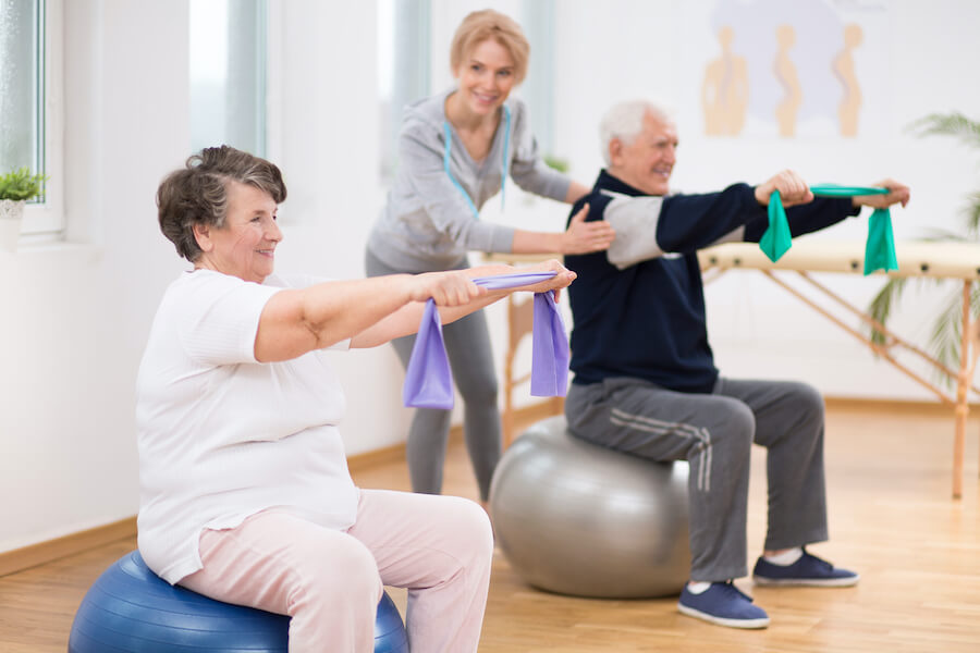 older woman and man exercising on ball