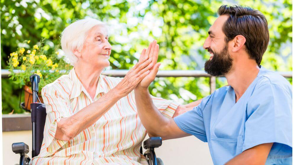young male nurse high five older woman