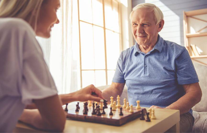 young woman and older man playing chess