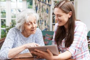 woman showing older woman tablet
